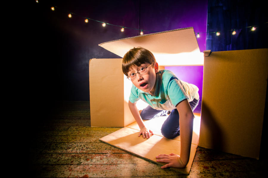 A child crawling in a box during Forts at Filament Theatre