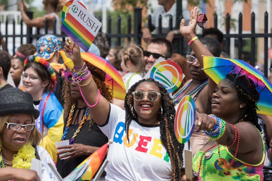 Friends wave rainbow flags at Pride Chicago