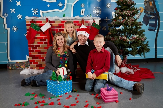 Photo of a family in front of a fake fireplace for Holiday Bricktacular
