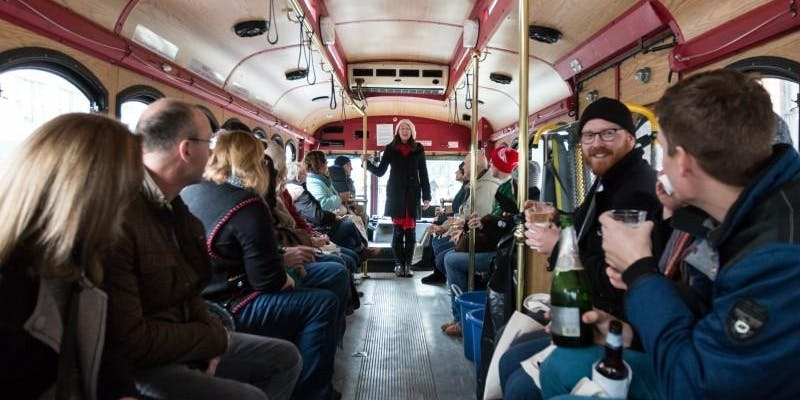 People drinking champagne on a bus for West Town Winterfest