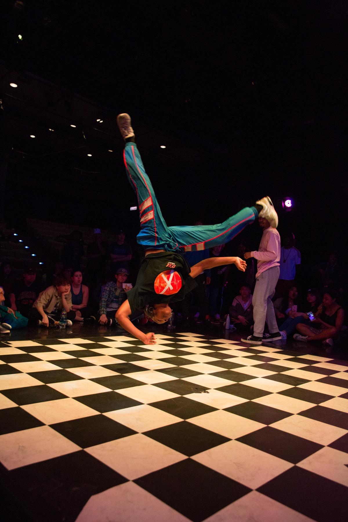 Man break dancing on a checkered floor