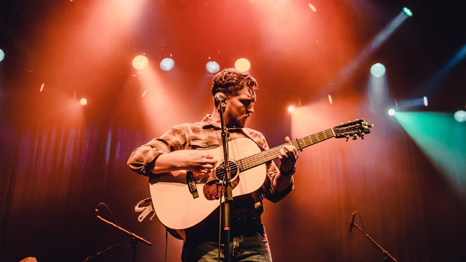 Tyler Childers playing a guitar on stage in Chicago
