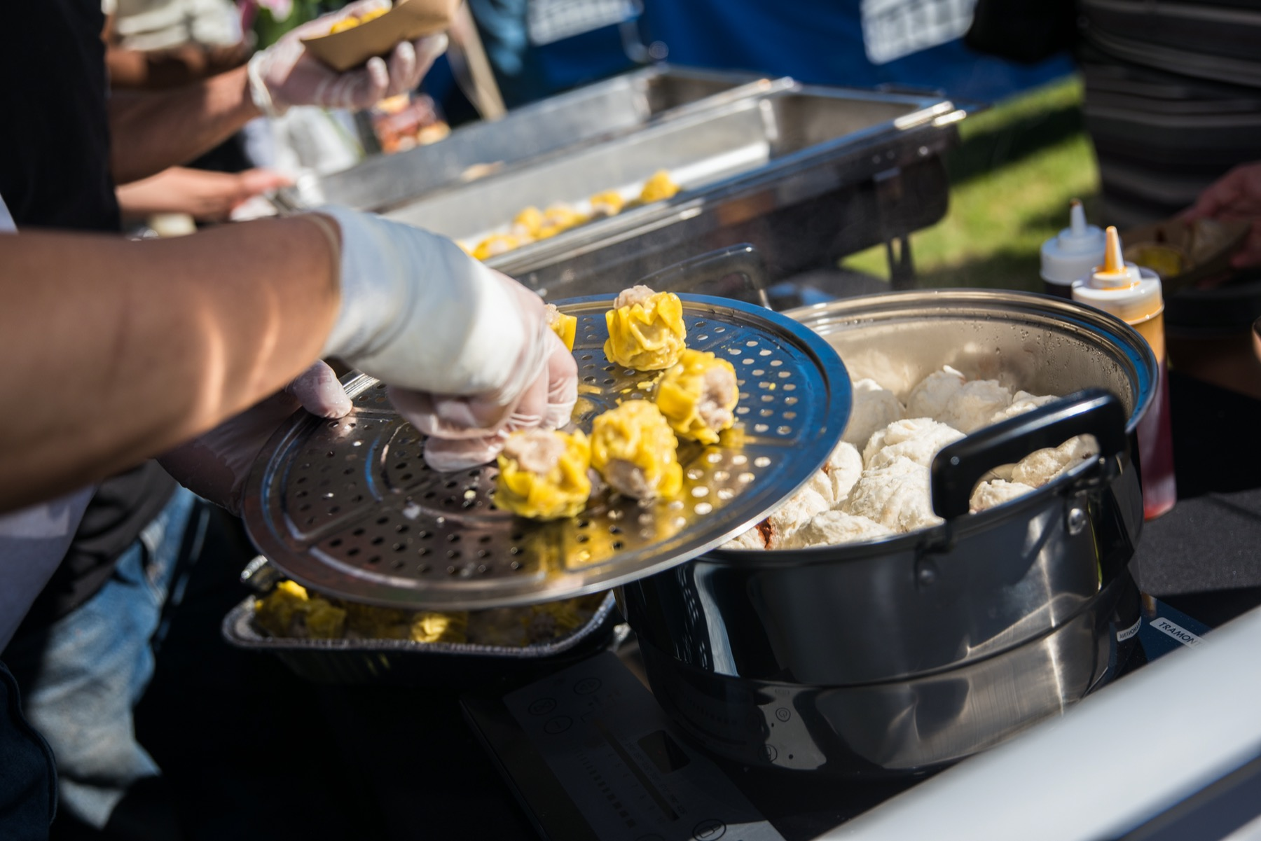 Man adding dumplings to cook at the World Dumpling Fest in Chicago