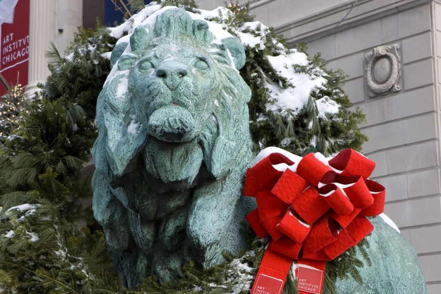 Snow-covered Lion statue with red bow at the Art Institute