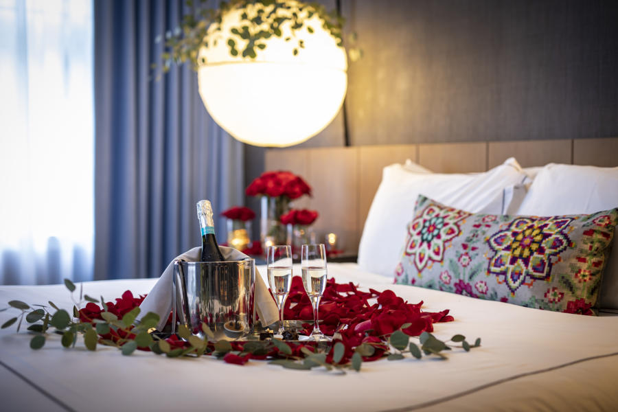 Rose petals and champagne on a hotel bed
