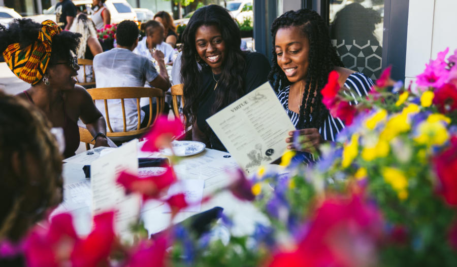 Friends dine on the patio at Virtue in Hyde Park