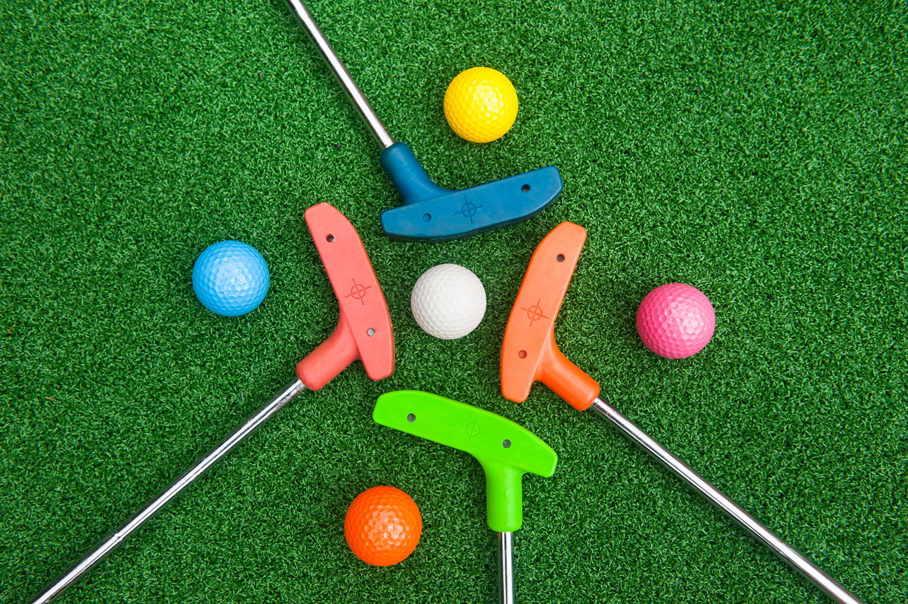 Four,Colorful,Golf,Putters,With,Golf,Balls,On,Synthetic,Grass